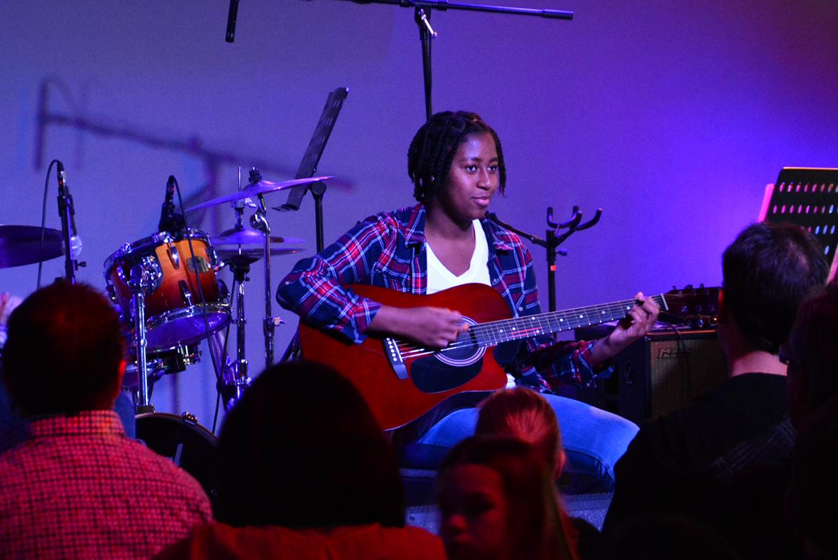 jeune femme jouant de la guitare sur scène